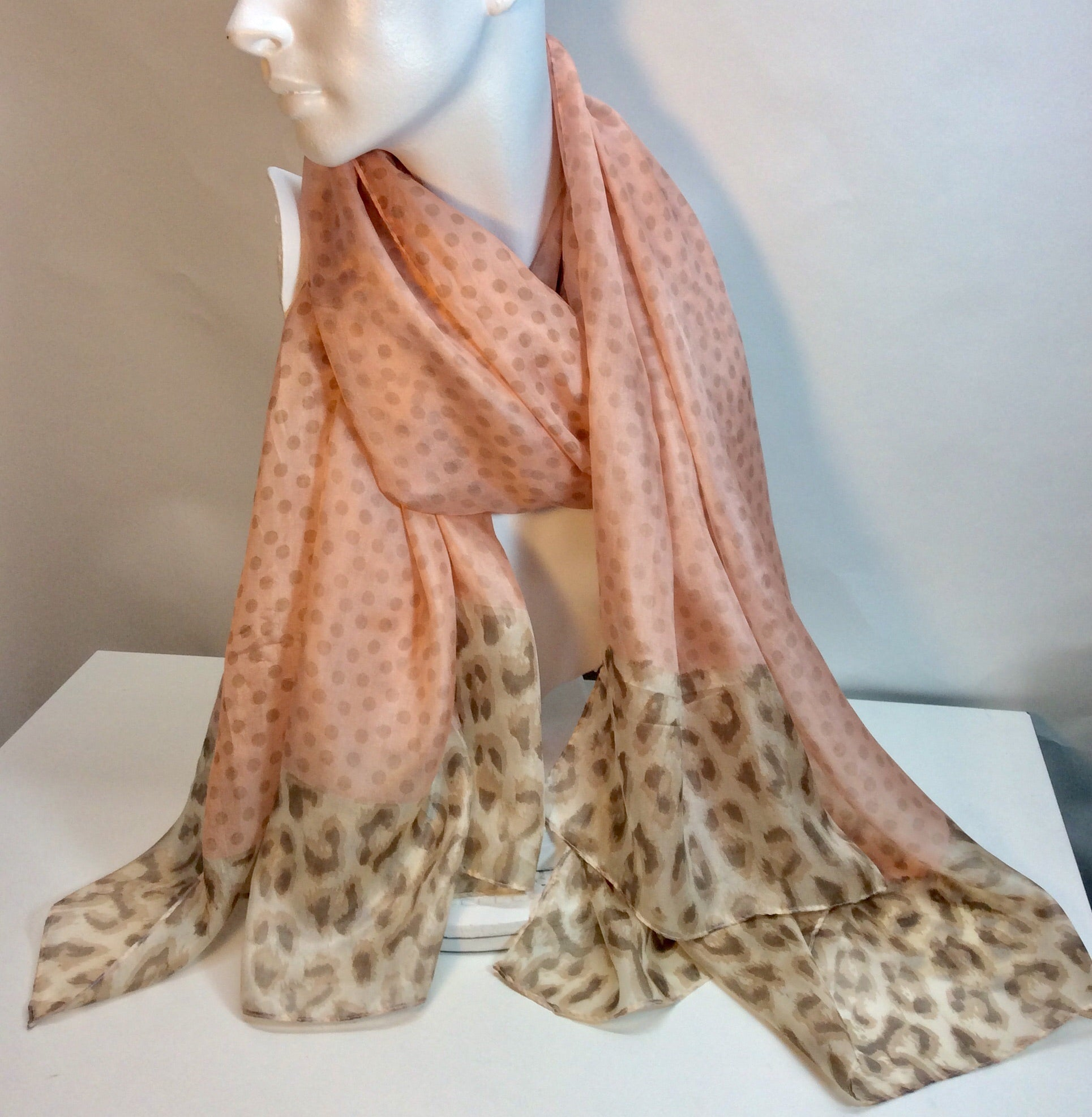 Spots on a soft coral background with animal print border on this silk scarf