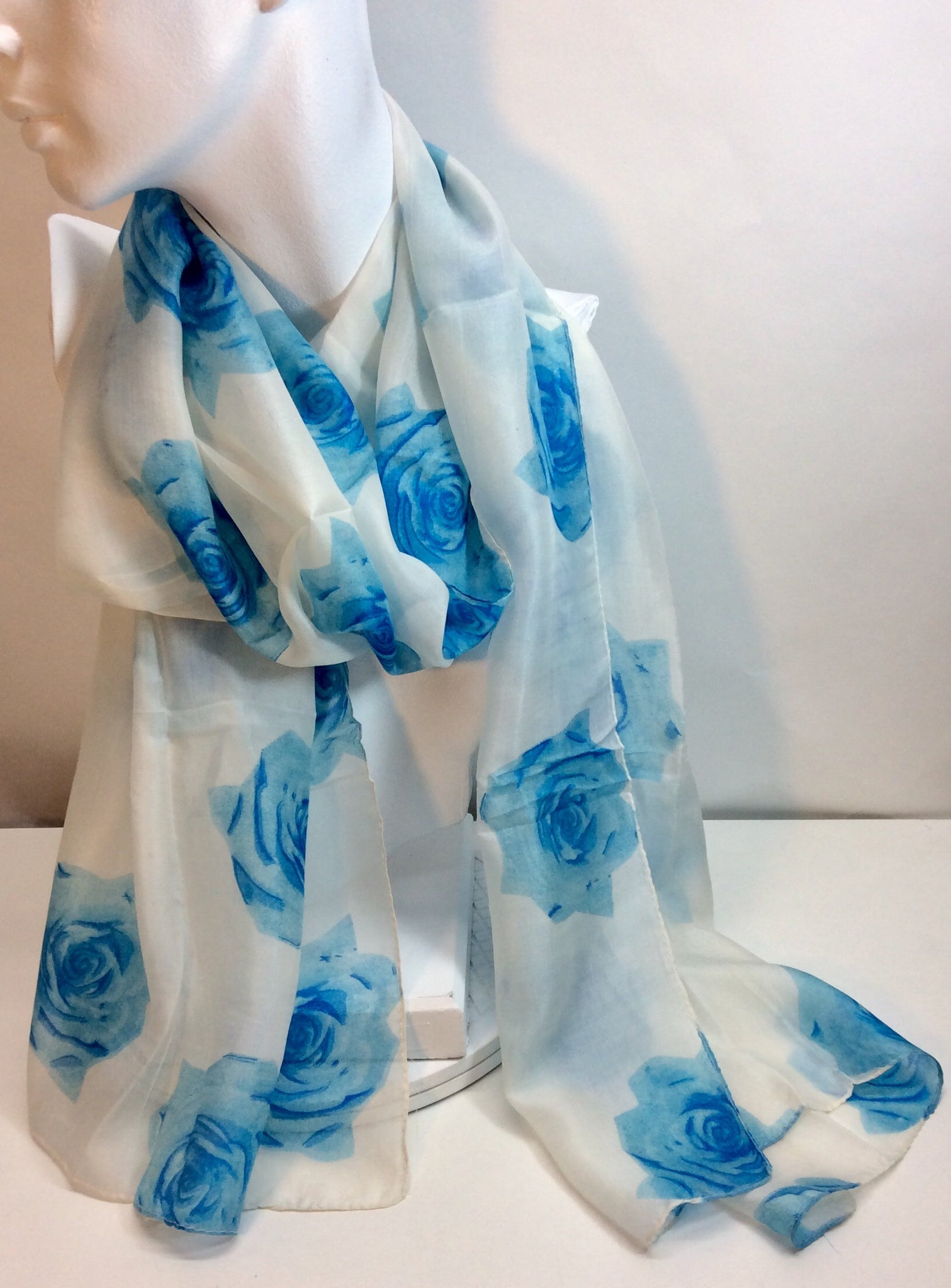 Gorgeous blue roses feature on this white silk scarf