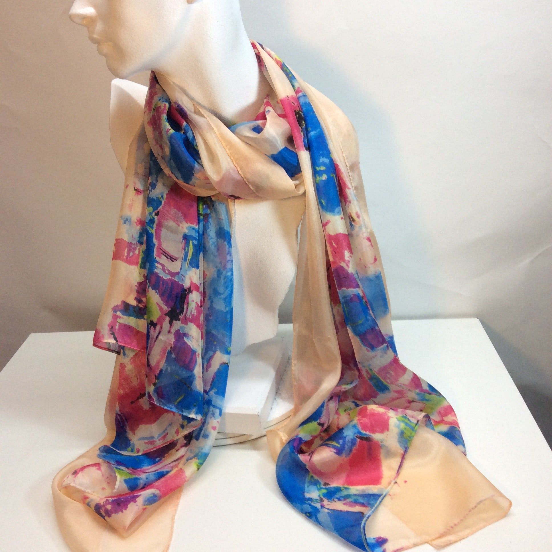 Abstract design of blues and pinks on shell pink background feature on this silk scarf