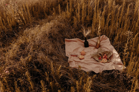 Bottles and baskets laid upon a blanket in a wheat field.