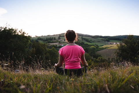 A person meditating on the ground with a view of grassy hills in the distance