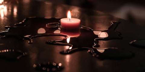 a small candle is burning low, melting wax into puddles on the surface