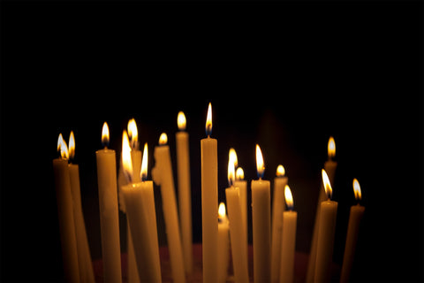 a dozen or two tall, taper candles, lit, against a black background