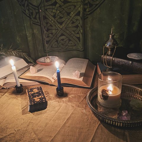 Candles upon an altar with an open book and a deck of tarot cards