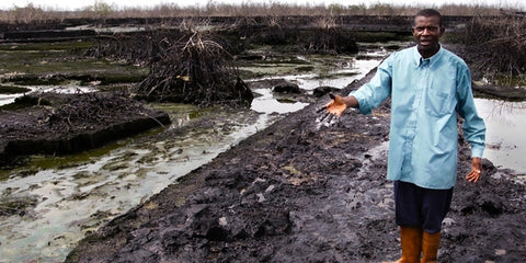 A man stands in a landscape devastated by oil spills, his hand outstretched to show the damage.
