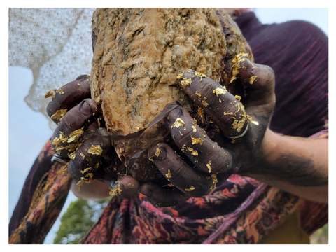 A witch witch fingers black from charcoal and covered in gold flakes holds a large beach rock. photo by Madeleine (Peach) Ingridsdotter