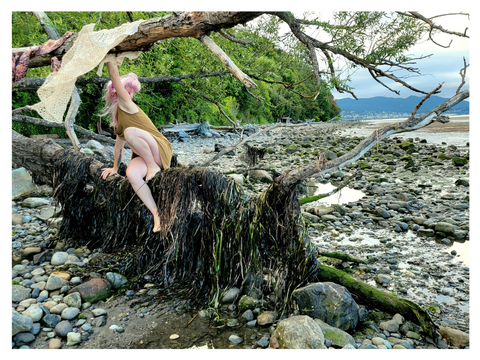 A woman with pink hair climbs along a horizontal tree over a rocky beach. photo by Madeleine (Peach) Ingridsdotter