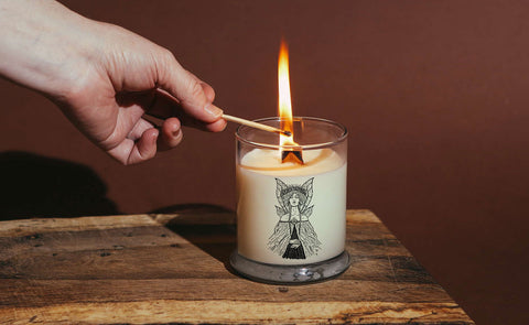 A Green Fairy candle being lit with a match