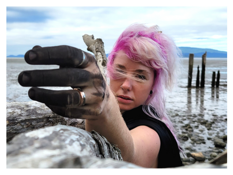 A wind-blown, pink-haired woman on a beach rests her arm on a tree branch, reaching toward the camera. Her fingers are blackened with charcoal. photo by Madeleine (Peach) Ingridsdotter