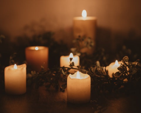 six thick pillar candles casting warm light, surrounded by flora