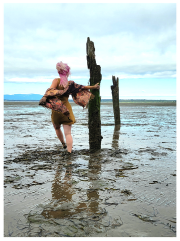 Sea Witch Botanicals founder Alesia Hall dances barefoot in the muddy low tide and high wind on the Pacific coast. She has pink hair and a mustard yellow dress.
