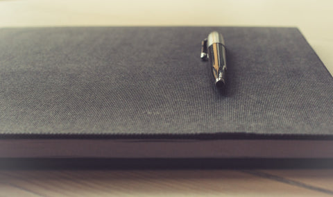 A journal resting on a table with a pen on top of it