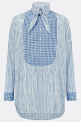 A loose long length cotton shirt in blue stripe with a contrasting blue check bib and cuff detail, front view, by A Child Of The Jago