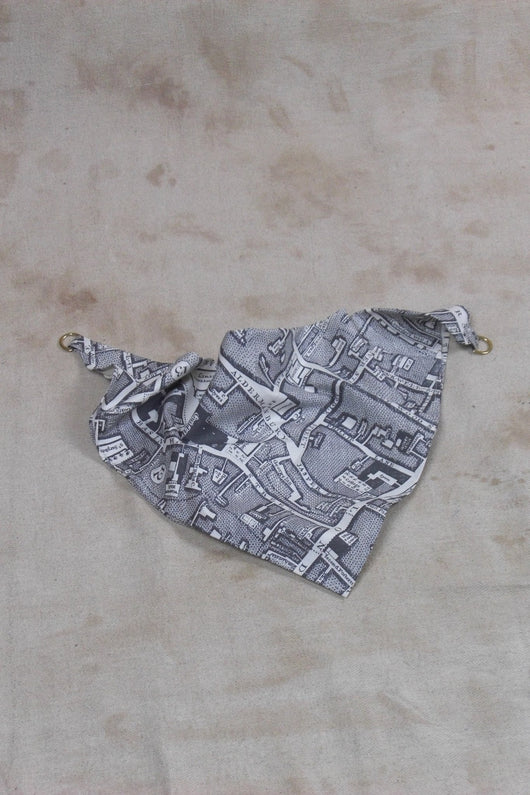A 100% cotton triangular shaped handkerchief in a grey boundary map print with two gold D-shaped rings on opposing sides, by Child Of The Jago