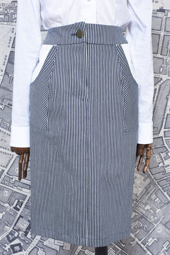 A streamlined pencil skirt in a stretch black and white stripe denim fabric with contrast pocket detail on a mannequin, front view, by A Child Of The Jago