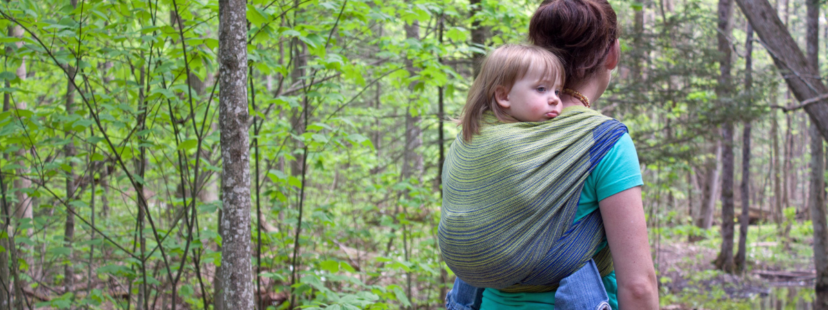 Image of a woman wearing a baby on her back in a woven wrap