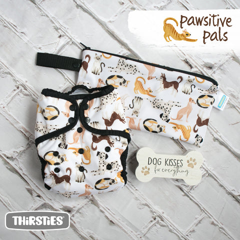 Image of Thirsties Pawsitive pals duo wrap and wet bag.  Diaper print has a dog print on it with a white background and diaper has black trim.