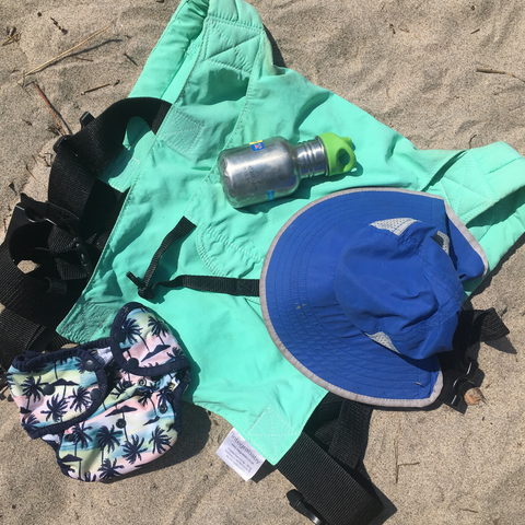 Image of Integra carrier laying on the sand at the beach with other beach items for a baby