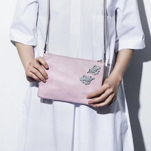 Model wearing Dentelle Magnetic Brooches in Slate on a Pink Purse