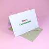 "Simple White Holiday Greeting Card in Bright Green and Red Font reading ""Merry Coronamas"", a little 2020 Humour displayed on a bright pink background"