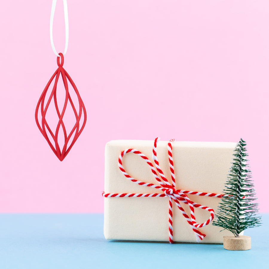 3D Printed Holiday Ornament in Crimson Red on a pink and blue background next to Holiday Gift and mini Christmas tree