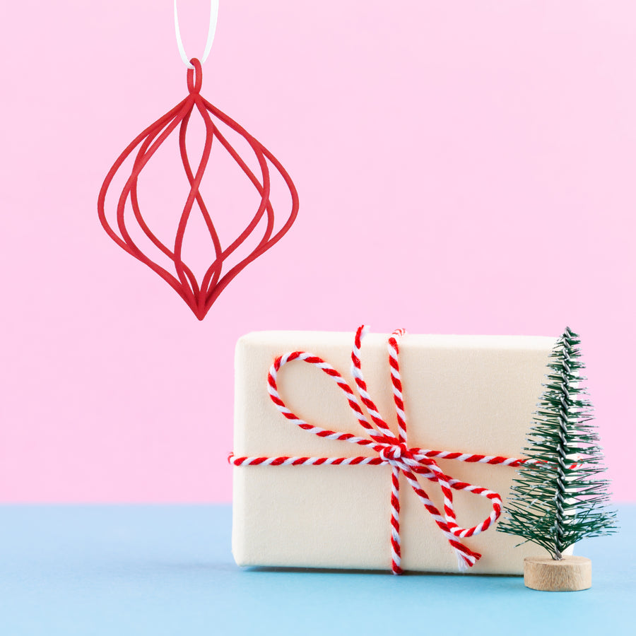3D Printed Swirl Holiday Ornament in Crimson Red on a pink and blue background next to a mini Christmas tree and holiday gift