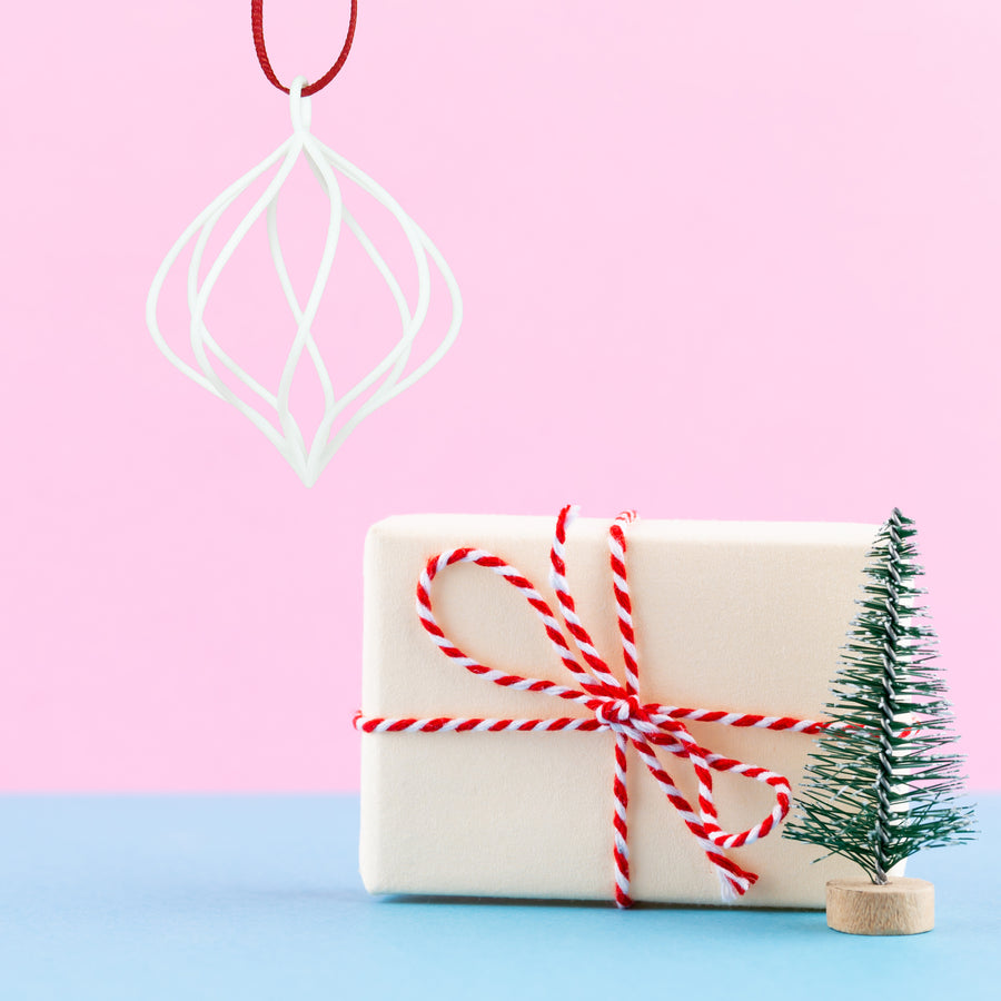 3D Printed Holiday Ornament in Crimson Red on a pink and blue background next to a mini Christmas tree and holiday gift