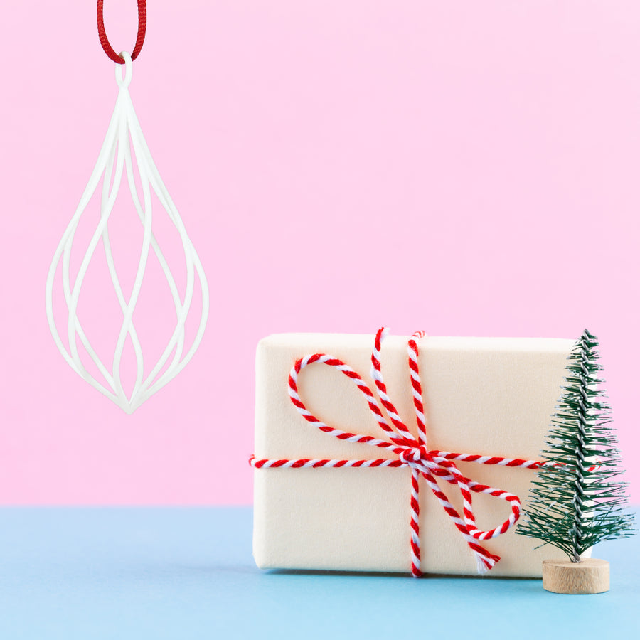 3D Printed Twirl Holiday Ornament in snow white on a pink and blue background next to a gift wrapped in kraft paper with a red and white ribbon and a mini Christmas tree