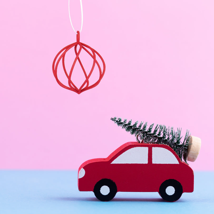 3D Printed Holiday Ornament in Crimson Red on a pink and blue background next to a red Toy car carrying a  mini Christmas tree