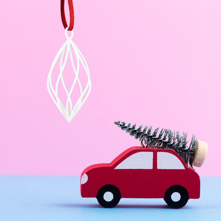 3D Printed Holiday Ornament in Snow White on a pink and blue background next to a red Toy car carrying a  mini Christmas tree