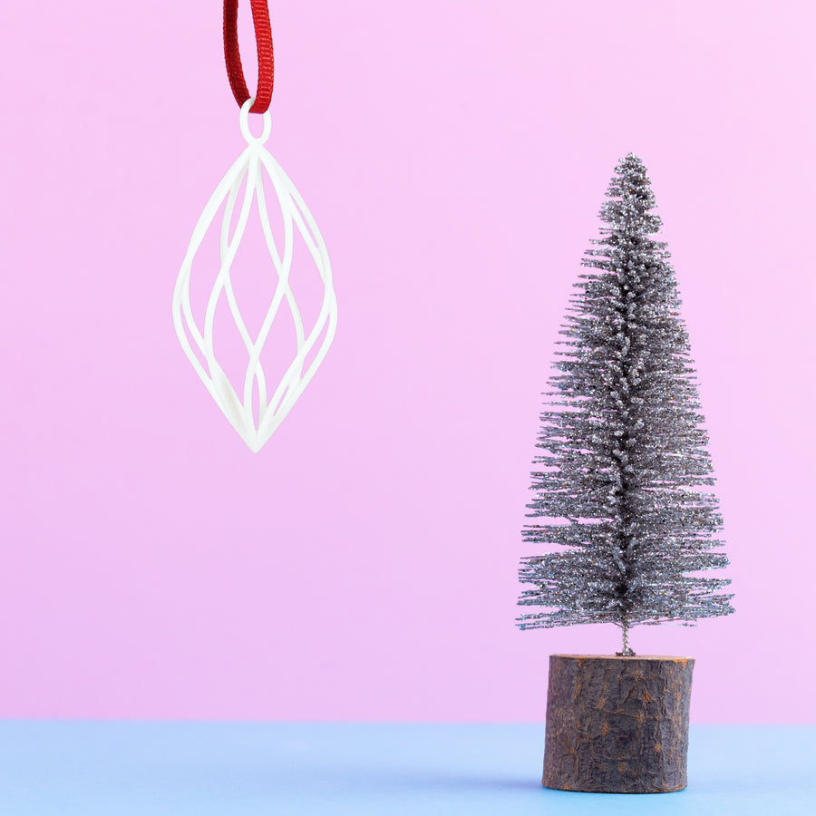 3D Printed Holiday Ornament in Snow White on a pink and blue background next mini Christmas tree