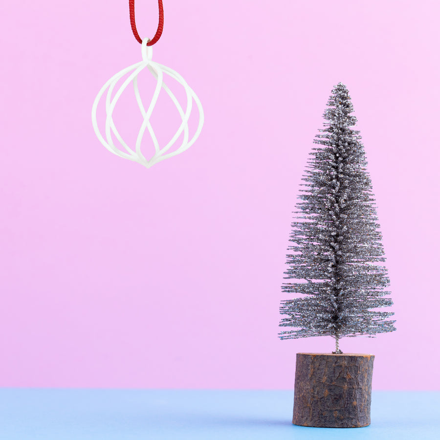 3D Printed Holiday Ornament in Snow White on a pink and blue background next to a mini Christmas tree
