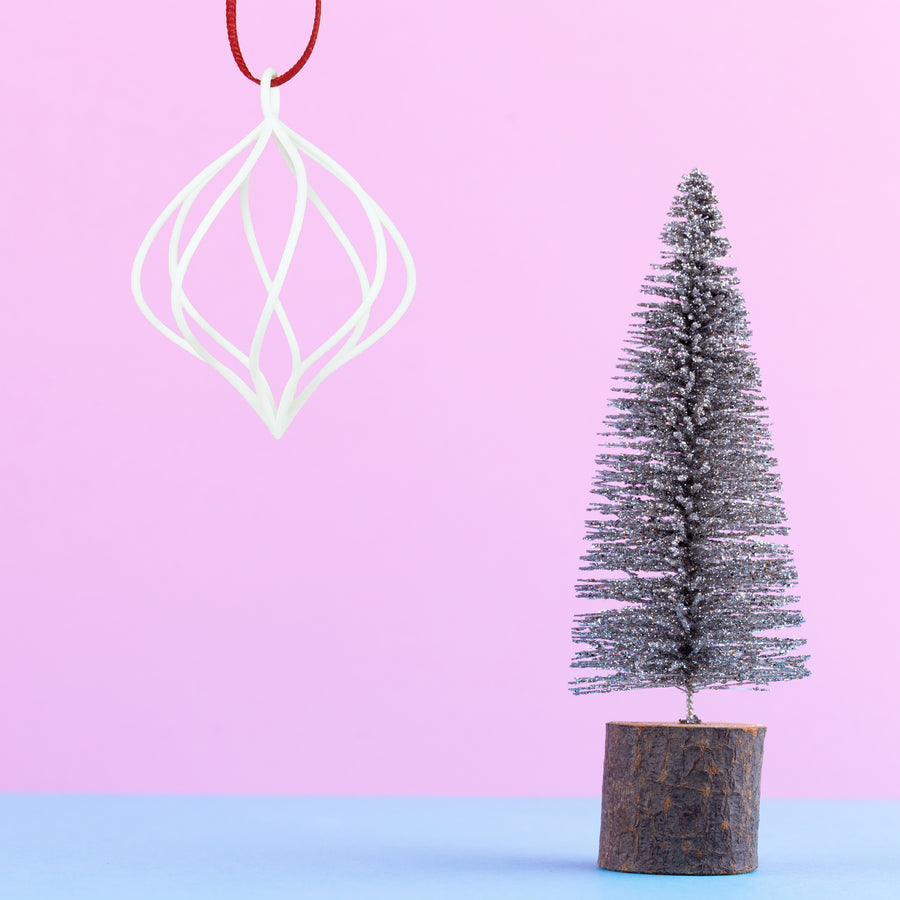 3D Printed Swirl Holiday Ornament in Snow White on a pink and blue background next to a mini Christmas tree