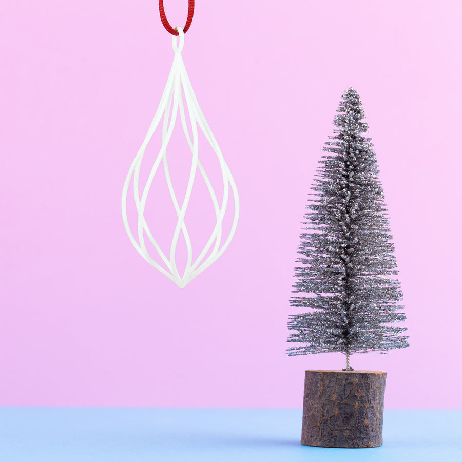 3D Printed Twirl Holiday Ornament in Snow White on a pink and blue background next to a mini Christmas tree