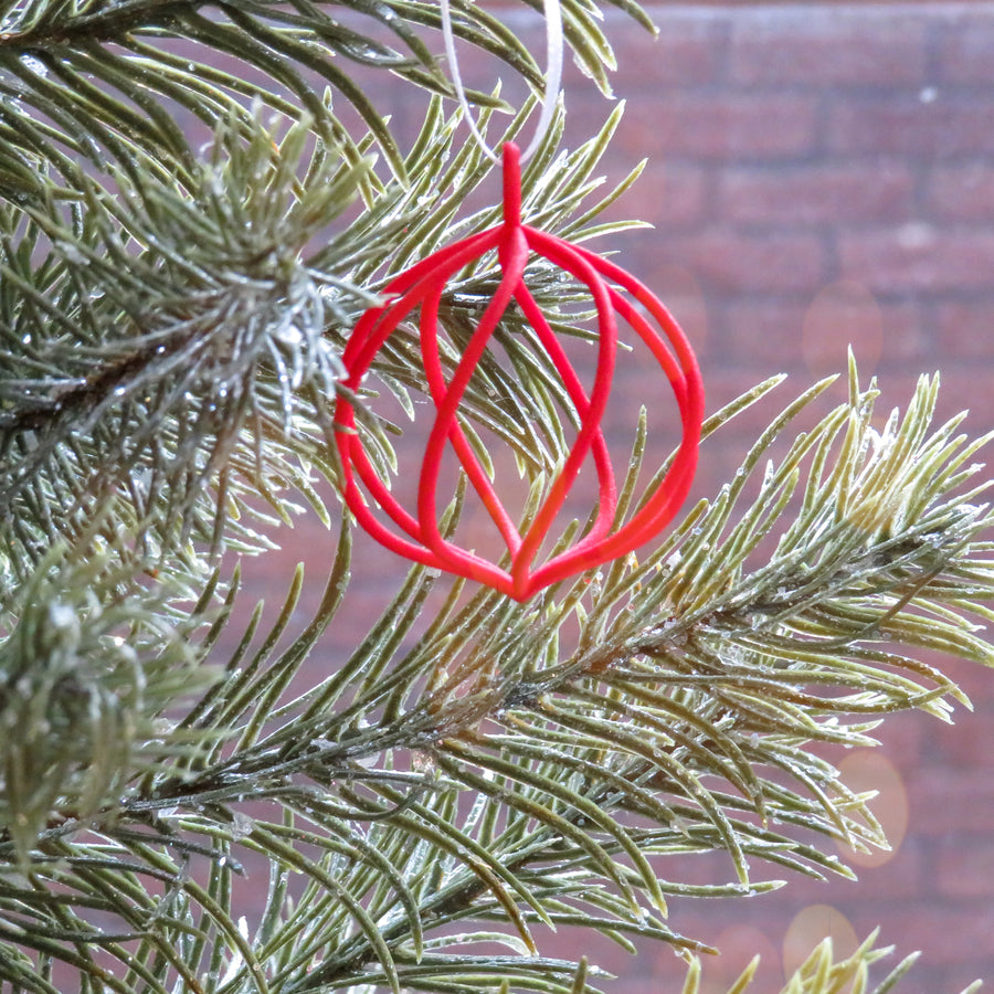 Jingle 3D Printed HOliday Ornament suspended on a Christmas Tree in Snow White