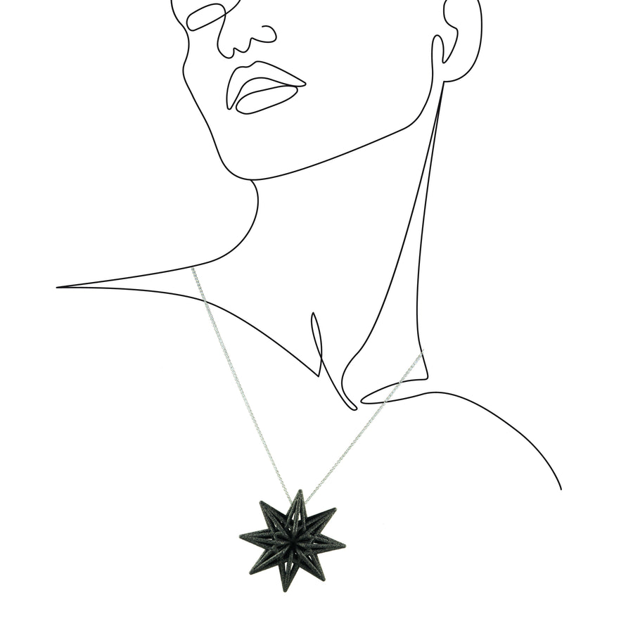 Our Starbright Pendant in carbon black on an outline sketch of a woman