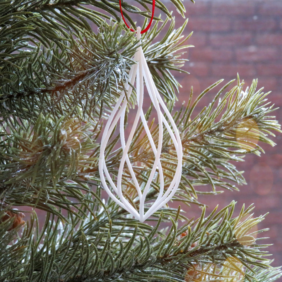 Twirl 3D Printed HOliday Ornament suspended on a Christmas Tree in Snow White