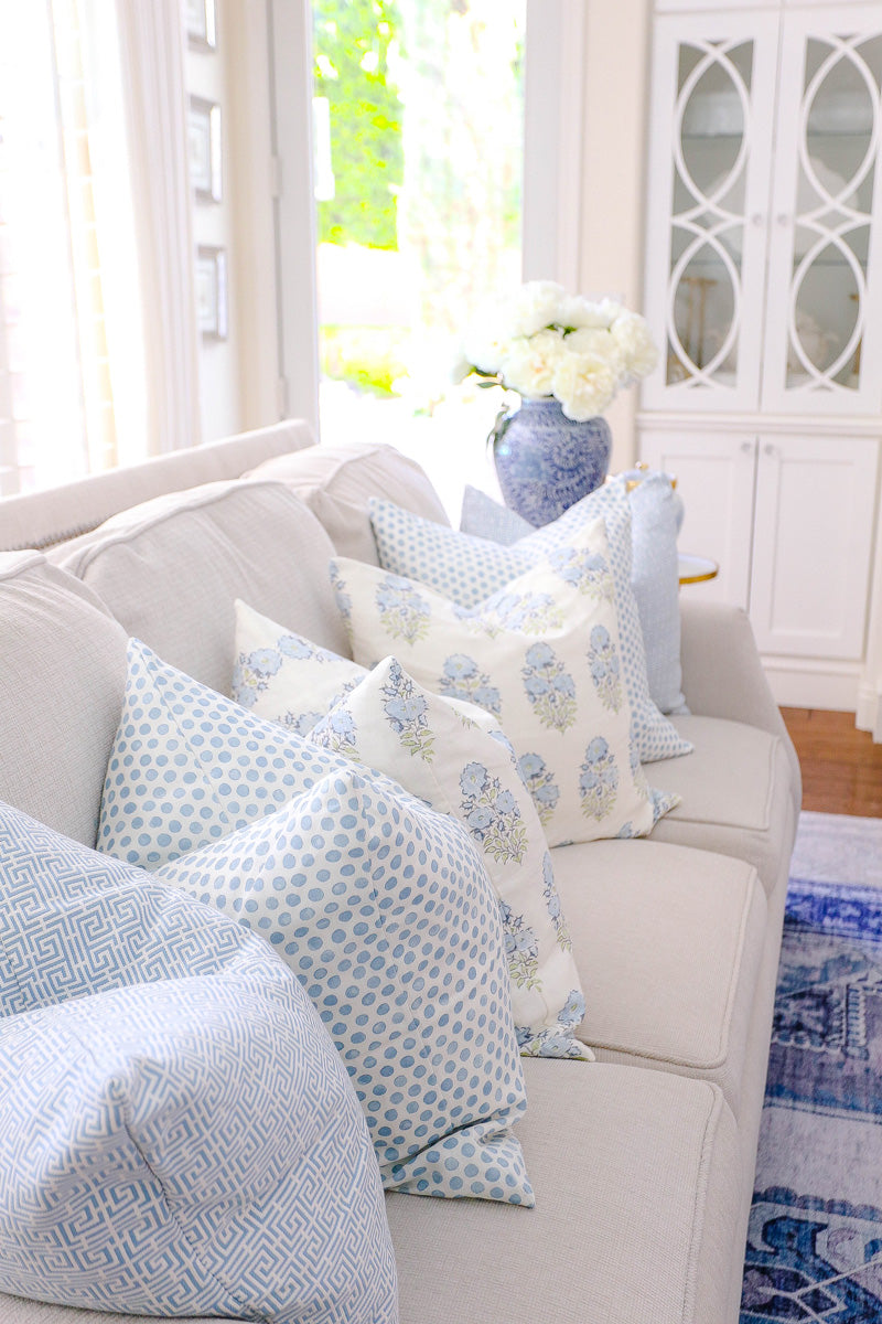 Blue and white patterned designer pillows on beige sofa from Arianna Belle Shop |  living room of Randi Garrett