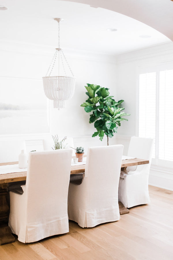 Designer Spotlight Kate + Amanda | Arianna Belle Blog | light-filled dining room with white slipcovered chairs, long wooden table and fiddle leaf tree