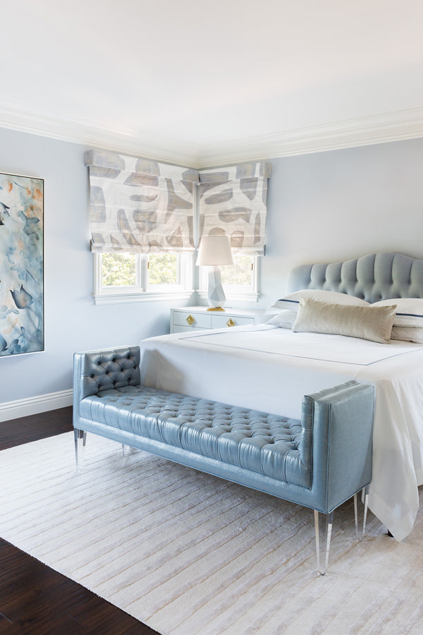 Designer Spotlight: Jenn Feldman | Blue bedroom with extra long decorative pillow tufted headboard bench at foot of bed and abstract art