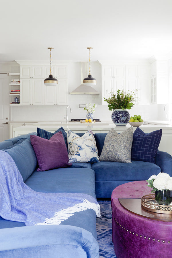 Designer Spotlight: Jenn Feldman | open concept white kitchen living room with blue sectional sofa and mix of designer decorative pillows
