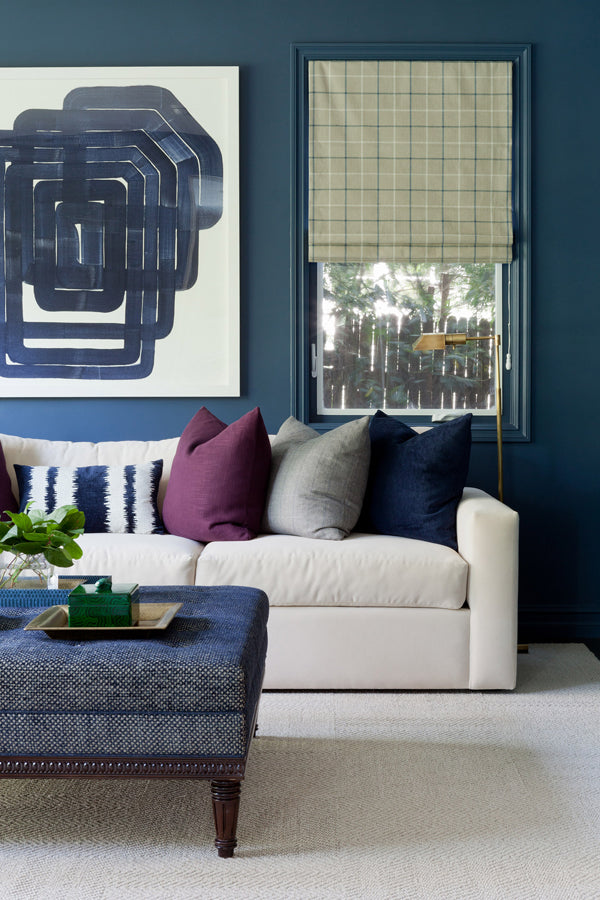 living room with dark navy walls abstract art and mix of designer pillows