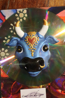 blue holy cow fridge magnet mounted on a CD