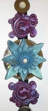 feng shui wall decor blue sculpted lotus centre surrounded by purple swirls and round mirrors