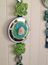 close up of green apple sculpted wall art dangle  w/ round mirror and white lotus