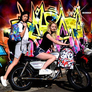 Girls with Bonne Classic Backpack posing on motorbike in front of a graffiti wall