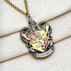 Harry Potter Jewellery Gryffindor House Crest Pendant Necklace with Medallion and Chain on textured background - Bronze-Gold
