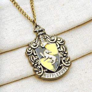 Harry Potter Jewellery Hufflepuff House Crest Pendant Necklace with Medallion and Chain on textured background - Bronze-Gold