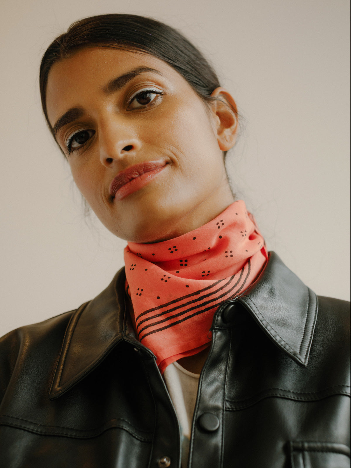Coral block printed bandana with a delicate black dot pattern and striped pattern