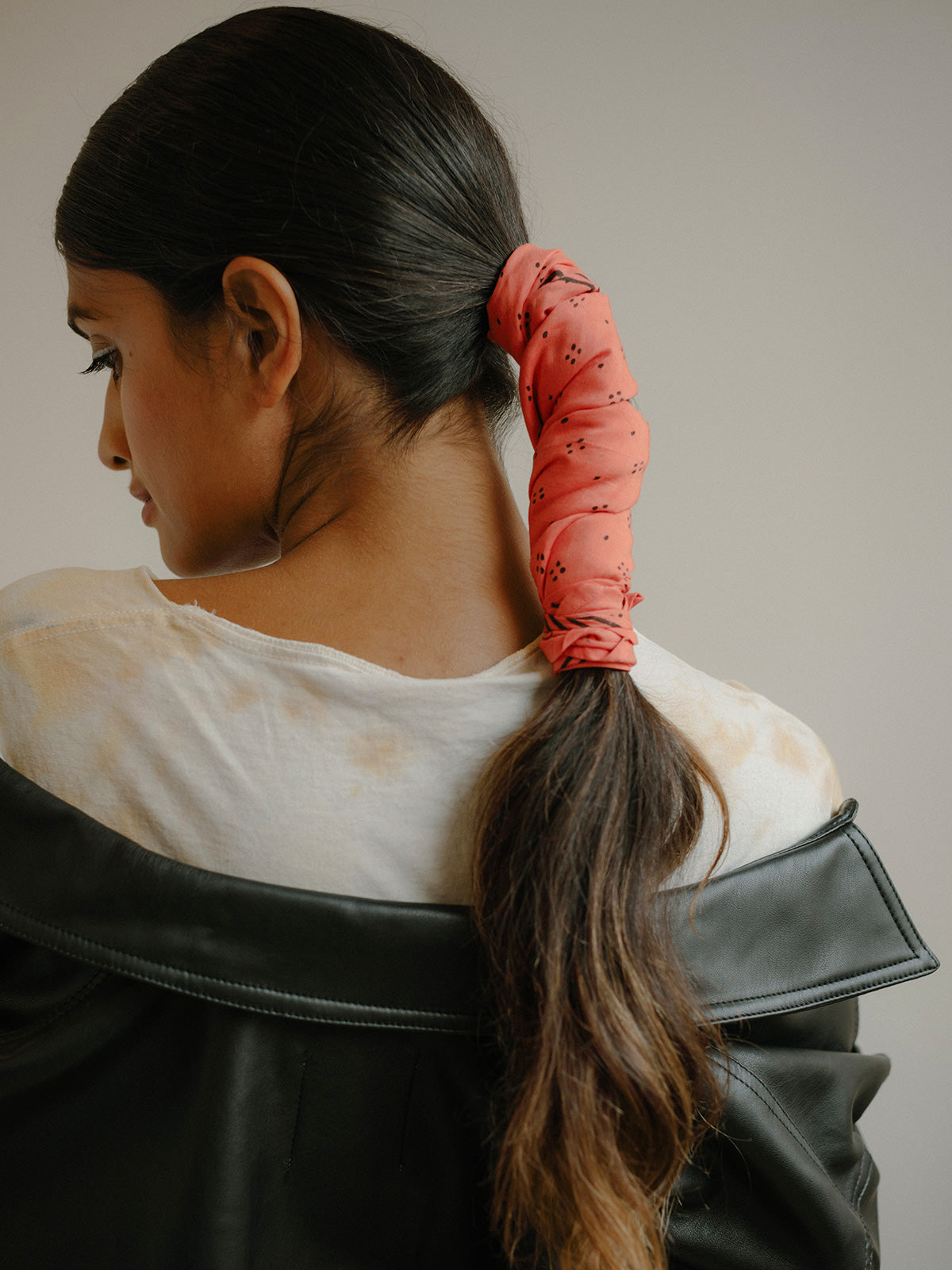 Ponytail with SUNDAY/MONDAY's coral Constellation bandana, featuring a delicate black block print pattern.